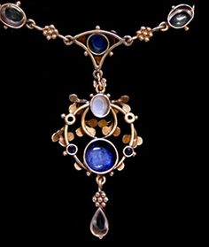 Jessie M King for Liberty & Co. An delicate Arts & Crafts gold necklace. The pendant set with cabochon sapphires and mother-of -pearl within a border of green enamelled leaves and small sapphires  with a moonstone drop. The enamelled chain set sapphires and moonstones. British. Circa 1900. Size: Pendant from centre drop 4.9 cm. Width 2.1 cm.  Total length around necklace 38 cm.  Lit.: 'Glasgow Girls. Women in Art & Design 1880-1920'. Edited Jude Burkhauser  Sold by Van den Bosch. Image 3 of…