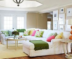 This casual living room knows how to step back and let the accessories and good bones do the work. A U-shape sofa anchors the room, while an an abundance of pillows, a gallery wall of art, and interesting architecture bring the space to life.  Via BHG.com