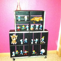 Chalkboard crate shelf on wheels displaying my daughters Smurf collection.