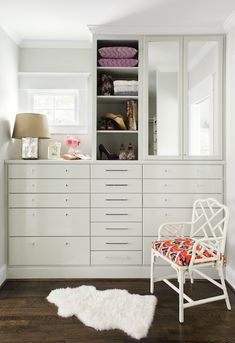 Beautiful walk-in closet with white built-in cabinets, mirrored doors, antique mercury glass lamp, white faux bamboo chair with coral & black ikat cushion and Ikea Rens.