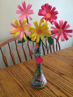 Construction paper flowers. Vase filled with gift-wrap ribbon.