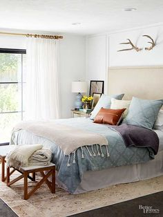 Clean lines, simple decor, and cozy materials make this master bedroom the best combination of relaxing and charming. A pair of thrifted stools at the foot of the bed are repurposed as a bench and a reupholstered headboard looks spendy but was purchased preowned.