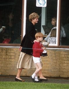 June 09, 1992: Prince Harry carries a trophy as his mother walks beside him. This would be his last sports day at Wetherby shcool.(x)