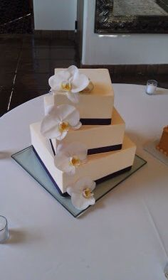A Square Wedding Cake Wrapped In Brown Ribbon With Fresh Purple Dendrobium Orchids By True Confections