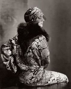 A model poses for Edward Steichen in Vogue (November 1925), wearing an embellished headdress by Suzanne Talbot and an ornate coat with fox c...