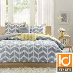 The charming Elle comforter set makes any bedroom fun and inviting. A gray and white chevron print runs along the comforter, while the reverse side is a solid yellow.