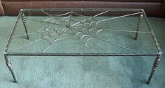 """Spider Web Coffee Table Designed and created by Wonderland Welding One of a kind coffee table, ornamental iron frame, steel spider web, and glass top. Measures 20""""x40"""" Have an idea in mind? I can work with you to design and create unique furniture and home décor."""