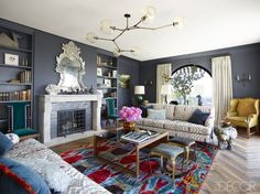 The living room of the Hollywood Hills home of Jamie Tarses and Paddy Aubrey, which was designed and renovated by Pamela Shamshiri of Commune Design. The sofas by George Smith are upholstered in an Oscar de la Renta for Lee Jofa fabric; the cocktail table is a custom design, and the stools from Hollywood at Home and wing chair are vintage. The ceiling fixture is by Lindsey Adelman, the vintage mirror is from JF Chen, the fireplace is original to the house, and the walls are painted in…