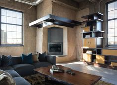 Industrial Loft in a Former Denver Flour Mill - dwell.com ________________________ The fireplace is located at the original chimney stack of the building. Robb Studio created a sculptural fireplace using exposed concrete, steel, and Shou-sugi-ban wood for the hearth seat. Photo by David Lauer
