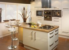 North East Direct Kitchens- really like the high gloss cream with wood effect work tops...classy and elegant