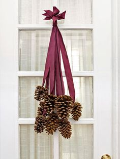 8 four to six-inch pinecones and 8 two-foot-long pieces of silk ribbon. Use a hot-glue gun to adhere the last two inches of each ribbon to the base of a cone. After the glue dries, collect all the ribbon ends and stagger them so that the cones fall at varying lengths. Tie the ribbon ends together in a knot, trim the tips so they are uniform, and slip the knot over a finishing nail.