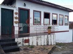 Casa colonial | PHOTOVIDEOBANK Foto casa colonial fachada exterior em rua de pedra com janelas típicas portuguesas alpendre.