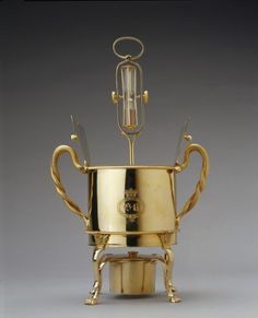Egg boiler for four eggs. This ingenious object forms part of a silver-gilt breakfast service presented to George III by his five youngest daughters on his sixty-sixth birthday, 4 June 1804. The King would have boiled his own eggs at the breakfast table by opening the double lid of the boiler and placing the eggs in the frame inside. Water inside was kept boiling by the lamp burner below, while the egg timer above ensured the perfect cooking time. Click link for more.