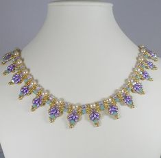 These gorgeous lavender glass, two hole Super Duo beads are woven into a scalloped edge with tiny golden seed beads and faceted Czech glass beads surrounding cream crystal pearls. Highlighted by green opal Swarovski crystals and small golden drops accent the textured edging. The total length is 18 with a spring ring clasp and 2 extender chain finished with a golden drop.  Design by Isabella Lam.  https://www.etsy.com/shop/IndulgedGirl