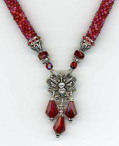 ROPE CROCHET NECKLACE  A mix of red-family beads creates interest and texture in this rope necklace. The red faceted glass beads and silver findings make a center piece that doubles as a clasp.