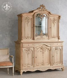CBVN1104  Graceful Antique Cabinet from France. Ornate handcarvings in old oak wood with a glass center cupboard door. Interior is a washed mineral white-grey.  91H x 67W x 24D  Circa: 1850  Eloquence Inc.