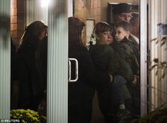 Heartbreaking: A boy believed to be Marcus, the son of tragic soldier Nathan Cirillo, is pictured being carried into a funeral home in Hamilton, Ontario, by a tearful relative on Friday in the wake of his father's remains
