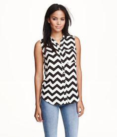 Straight-cut, sleeveless blouse in woven fabric. Collar, chest pocket, and buttons at front.