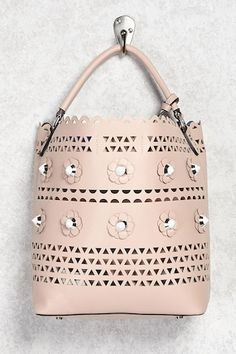 This 2-in-1 faux leather shoulder bag features a front daisy design with hardware center embellishments, geo laser cutouts, a detachable crossbody strap, a rolled top handle, and a snap-button top closure. This also includes a zip-top pouch and a zip-front wristlet.