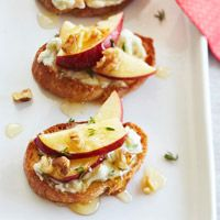 Ricotta, Gorgonzola, and Honey spread on baguette slices with thinly sliced apples and toasted walnuts