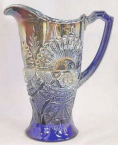 *RISING SUN (blue) Carnival Glass Pitcher: This style of pitcher has a flat bottom. The pictchers in the pattern are considered rare, especially in blue. Tumbler intended for this pitcher are scarce in either size and in either marigold or blue. A rare tray is also known in this pattern, found in blue.