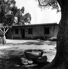 """(1964)* - Courtyard view of Hugo and Victoria Reid's adobe at the Arboretum. Well is at the left and rocks at right are believed to be the original baptismal font from one of the early California missions. The ranch was owned by E. J. """"Lucky"""" Baldwin from 1875 to 1909. Location: Los Angeles State and County Arboretum, 301 N Baldwin Ave, Arcadia."""