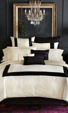 Super sophisticated, luxurious cream and black bedding against a pure black wall with gold framed blackboard. Purple carpet and ribbon with mistletoe hung behind the bed add to the wit of the scheme. And the chandelier - no other type of lighting could have been used.: