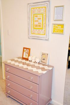 Gray dresser with fun, simple design on top. Cute frames above.
