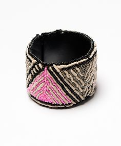 Grey, black, and an unexpected pop of pink adorn this elegant leather cuff. #noonday