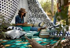 *A woman sitting outdoors, under an improvised tent, made of curtains with different black and white patterns. And she is surrounded with lots of cushions in colorful patterns.