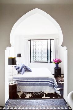 A traditional arabesque arch filled with modern costal decor makes this bedroom The Coastal Moroccan Home Getaway Of Your Dreams