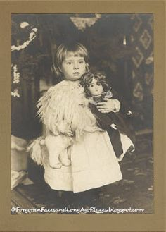 Adorable little girl holding her doll and what looks like a stuffed lion or horse.