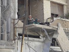 A man rests at his damaged house in Homs, June 5, 2012. REUTER/Waleed Fares