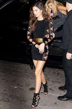 Lily Aldridge wears a Balmain cutout minidress with a gold belt and strappy sandals