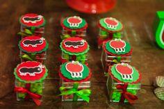 """Pequenas caixas de acrílico, cheias de balinhas coloridas, foram colocadas entre os doces da festa, que teve piquenique como tema. Feitas pela Papel Charmoso (instagram.com/papelcharmoso), elas foram enfeitadas com desenhos de maçãs e formigas, feitos com a técnica """"scrapbooking"""" (tipo de arte em papel)"""