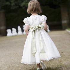 A beautiful flower girl dress a with a green silk sash