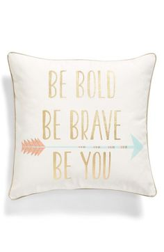 A stylized arrow graphic is stamped on a cute canvas accent pillow alight with metallic 'Be Bold, Be Brave, Be You' lettering.