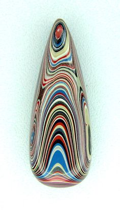 Fordite Motor Agate Cabochon - According to Wikipedia, Fordite, also known as Detroit agate, is old automobile paint which has hardened sufficiently to be cut and polished. It was formed from the build up of layers of enamel paint slag on tracks and skids on which cars were hand spray-painted (a now automated process), which have been baked numerous times. In recent times the material has been recycled as eco friendly jewellery.