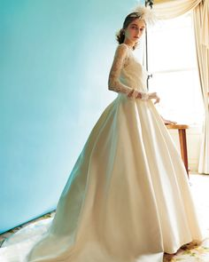 『時を超えて愛されるクラシカルエレガンスの最新形』 清楚な印象のロングスリーブドレス。 光沢のあるサテンスカートに描かれるドレープにうっとり。 Dress: DCL035(アーネラクロージング)