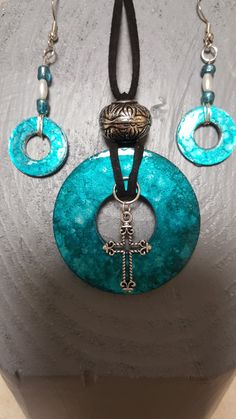 Washer pendant with alcohol ink. Finished off with cross charm, cording and a bead. Complimented  with washer earrings also with alcohol ink. Finished off with beads.