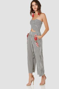 Chic tube jumpsuit with center cut out and floral patch detailing. Stripe pattern throughout with back zip closure.