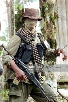 A soldier from the Autodefense Forces of Colombia paramilitary group waits before a training session in the El Placer area of Putumayo 22 October, 2000. The Revolutionary Armed Forces of Colombia guerrilla movement is holding a month-long transport stoppage in Putumayo, during which several clashes between the two groups have been reported. A guerrilla commander reportedly announced the stoppage will not be lifted until the government gets rid of the paramilitary groups and stops…