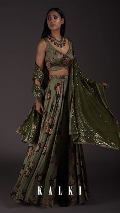 Wear this Milano satin Lehenga in laurel green tone with printed florals for an unforgettable appeal. It's the right kind of inspiration for you to believe that even a simple outfit can totally work wonders - even as occasion wear. The bustier with its exquisite V neck is further highlighted with scattered sequins and hand embroidery. The lehenga is all about chic, couture and pure simplicity with a fully sequined dupatta!  Dress Indian Style, Indian Wear, Indian Suits, Designer Party Wear Dresses, Desi Clothes, Occasion Wear, Sarees Online, Simple Outfits, Lehenga
