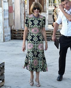 She's smiling! Editor-in-chief of American Vogue Anna Wintour flashed her pearly whites while clad in a green, black and pink patterned frock