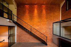 O concreto aparente na fachada equilibra as cores do exterior e valoriza as esquadrias desalinhadas. Piso de cimento queimado, paredes de tijolinho, telha metálica e teto revestido com chapas de compensado dão aconchego. Nas salas, a estrutura metálica foi mantida e restaurada para agregar valor ao conceito industrial aplicado ao projeto, remetendo os antigos galpões e lofts nova-iorquinos. #arquitetura #architecture #interiores #interiors #design #concrete #tijolinho #brick #loft…