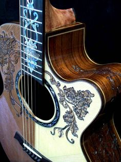 """A beautiful, all handmade acoustic grand concert guitar with """"Floral"""" theme carvings on the body and headstock"""
