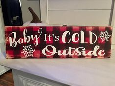 "This adorable sign features my favorite buffalo check pattern as the background and Baby it's Cold Outside is the perfect holiday song. Fully hand painted with a final coat of poly. Measures approximately 7""x24"" Includes a sawtooth hanger *please contact me if you'd like another"