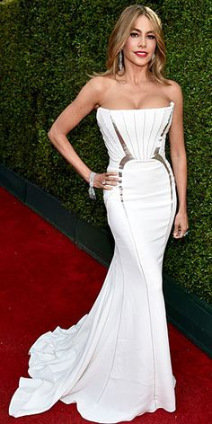 Sofia Vergara goes surprisingly simple and sleek in a white column dress with architectural silver detailing.
