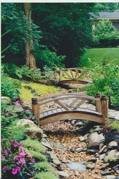 Wooden bridges over creek edged in stone for backyard landscape: Poynter Landscape Architecture