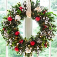 Christmas wreath with red and silvery balls and ornaments hung from a window.
